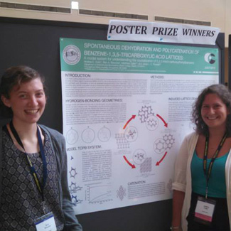 Two students in front of a scientific poster under the heading Poster Prize Winners