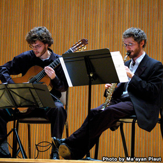 A musical duo with acoustic guitar and soprano saxophone