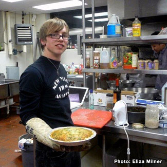 Daniel holds a hot dish in a food service kitchen