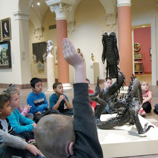 A grade school class learns about a sculpture at a museum