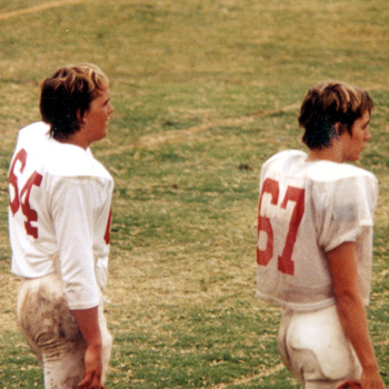 Two football players in the 1980s wearing numbers 64 and 67