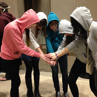 Five people in hooded sweatshirts form a circle and join their hands at the center