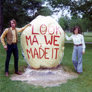 Two people in groovy 1970s attire pose by a boulder painted with the words, Look Ma, We Made It