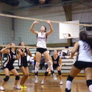 A volleyball player jumps for a ball high above the net