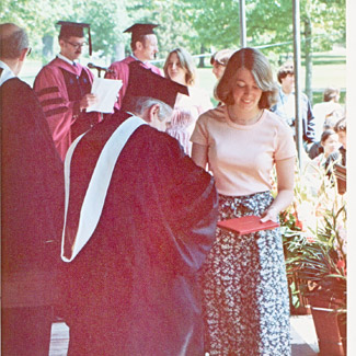 A 1970s-era student receives her diploma at Commencement