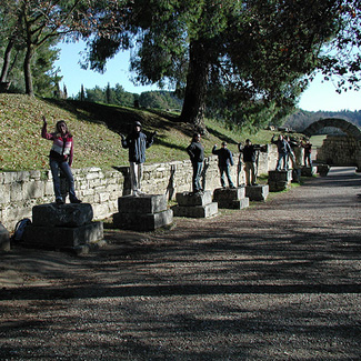 Students pose as statues by a stone wall