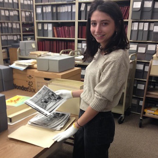 Eva wears gloves while handling photographs in a file room