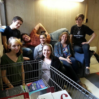 A group of friends with a shopping cart full of books