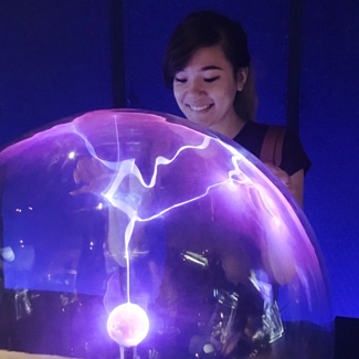 A student touches a transparent globe that contains bolts of electricity