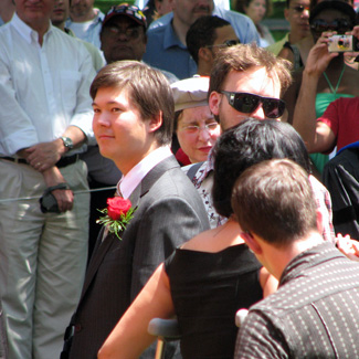 Young man in a crowd wearing a boutonnière on his suit jacket