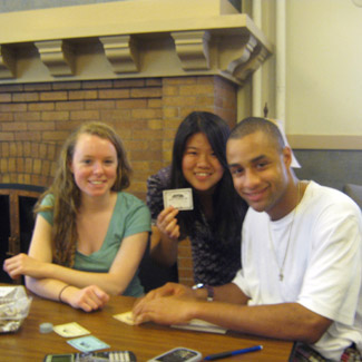 Three students at a table with calculators. One holds up a card.