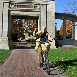 An older man with a raised fist rides a bike through Memorial Arch