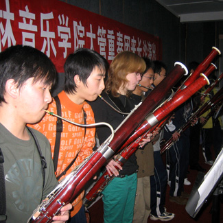 A row of bassoonists performs under a banner with Chinese characters