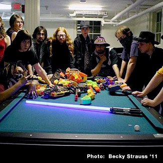 SciFi residents gather around a hoard of toy laser guns and light sabers spread out on a pool table