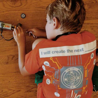 Wering a shirt that reads 'I will create the next [blank space]', Lauren tinkers with a device
