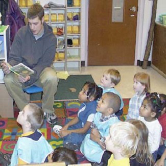 A college student reads to agroup of attentive preschoolers
