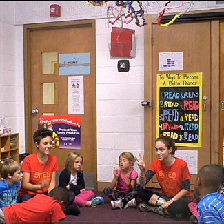 Two students wearing 'SITES' shirts sit in a circle with young children in a school classroom