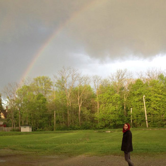 Lena stands under a rainbow