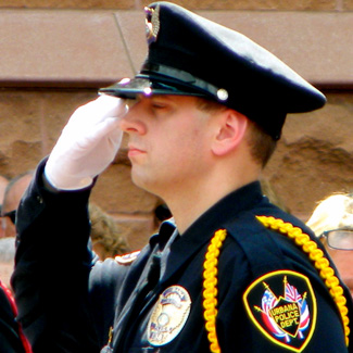 Matt salutes. He is wearing the dress uniform of the Urbana Police Department.