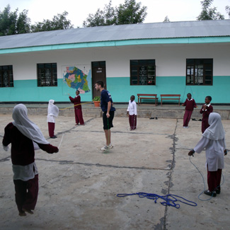 In a school courtyard, Mike teaches jump rope to a group of boys and girls.