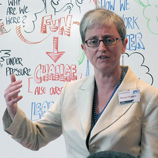 Nancy speaks in front of a whiteboard with phrases including Fun → Change, under pressure, why are we here?
