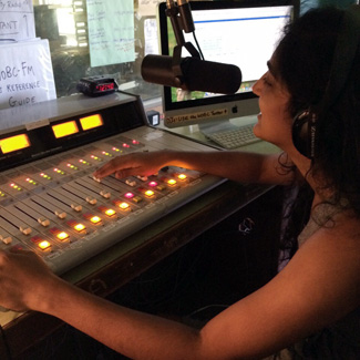 Nandita adjusts sound levels on the mixing board.