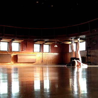In an empty dance studio, Natalia lays on her back with feet raised toward the ceiling.