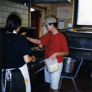 Two students cook food on a large stove.