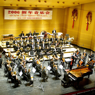 An orchestra on stage under a banner with Chinese characters and '2006 New Year Concert'.
