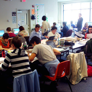 A dozen activists work intently with computers and papers