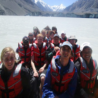 A group of people seated in a boat on a mountain lake.