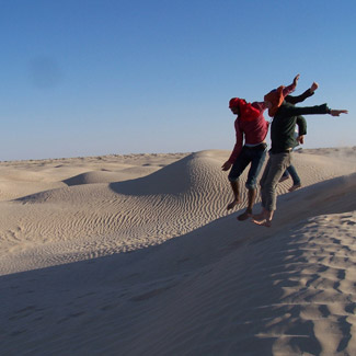 With only sand visible to the horizon, three people jump off a dune.
