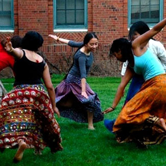 Women in colorful skirts dance in the quad.