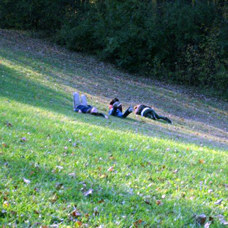Three friends lay in the grass on a hillside.