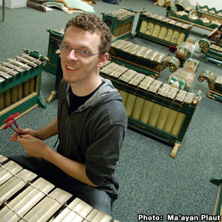 Sean is positioned at one section of a sprawling Gamelan. Many of the pieces resemble xylophones.