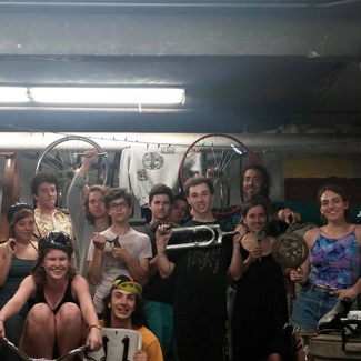 Members of the co-op pose holding bike parts.