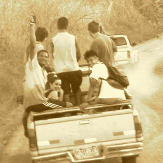 Group of people riding in the back of a pickup truck.