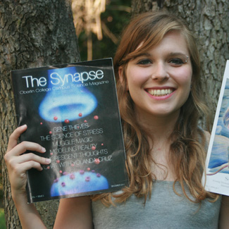 A woman shows the front cover of The Synapse magazine.