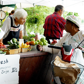 A woman asks a question at a fruits & vegetables stand.