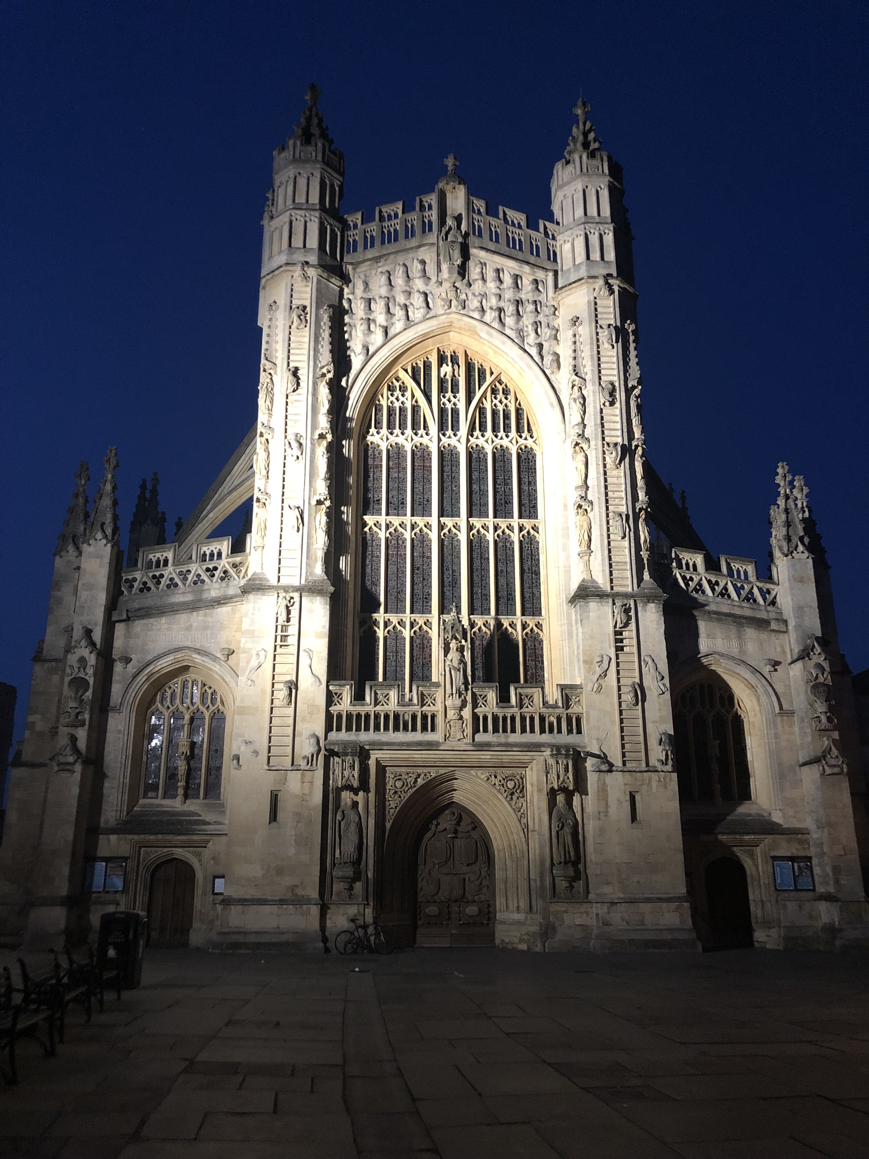 In front of a dark blue night sky is a large Gothic cathedral. It is illuminated by spotlights pointed up at it from the ground. The abbey has many spires, buttresses, windows, and statues. In front of the abbey is an empty town square.