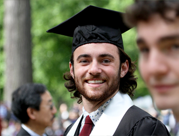 A smiling graduate in cap and gown
