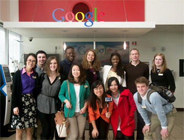 A group of people stands below a Google sign
