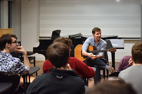 Chris Eldridge holds an acoustic guitar while teaching a class.