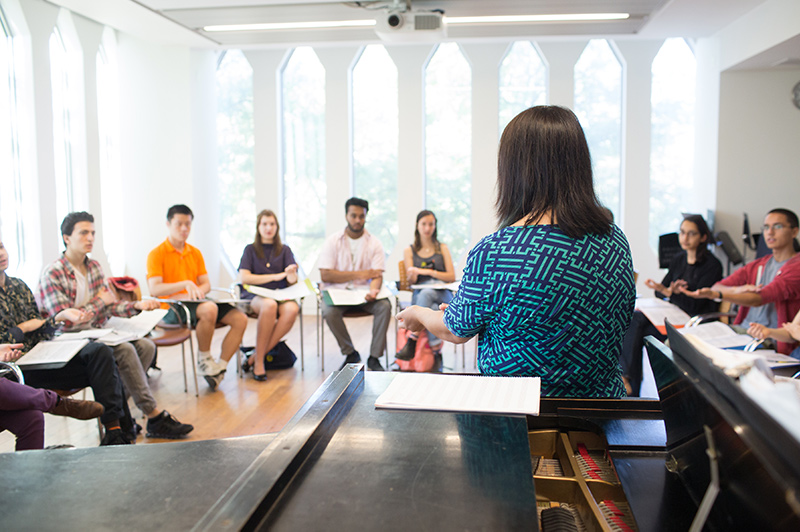 Students seated in a bright classroom. The professor is by a grand piano.