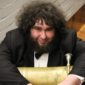 Bearded man in a tuxedo with a tuba on his lap