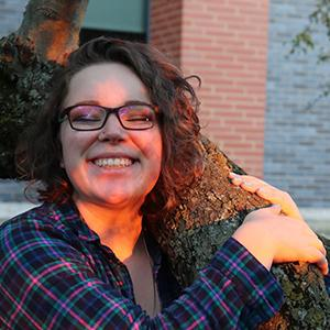 Emma grabs onto a tree branch and smiles