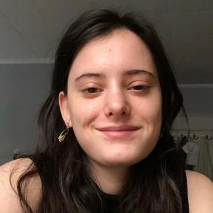 A photo of Meredith, a smiling young white woman with brown hair.