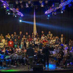 Orquesta Participativa with a large group of singers and musicians on stage.
