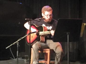 A guitarist is seated by microphones and a music stand
