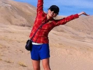 The author posing for a photo in a desert